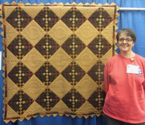 Donna Bozeman with Kansas Troubles quilt deigned and pieced by Donna at Machine Quilters Expo, April 2015