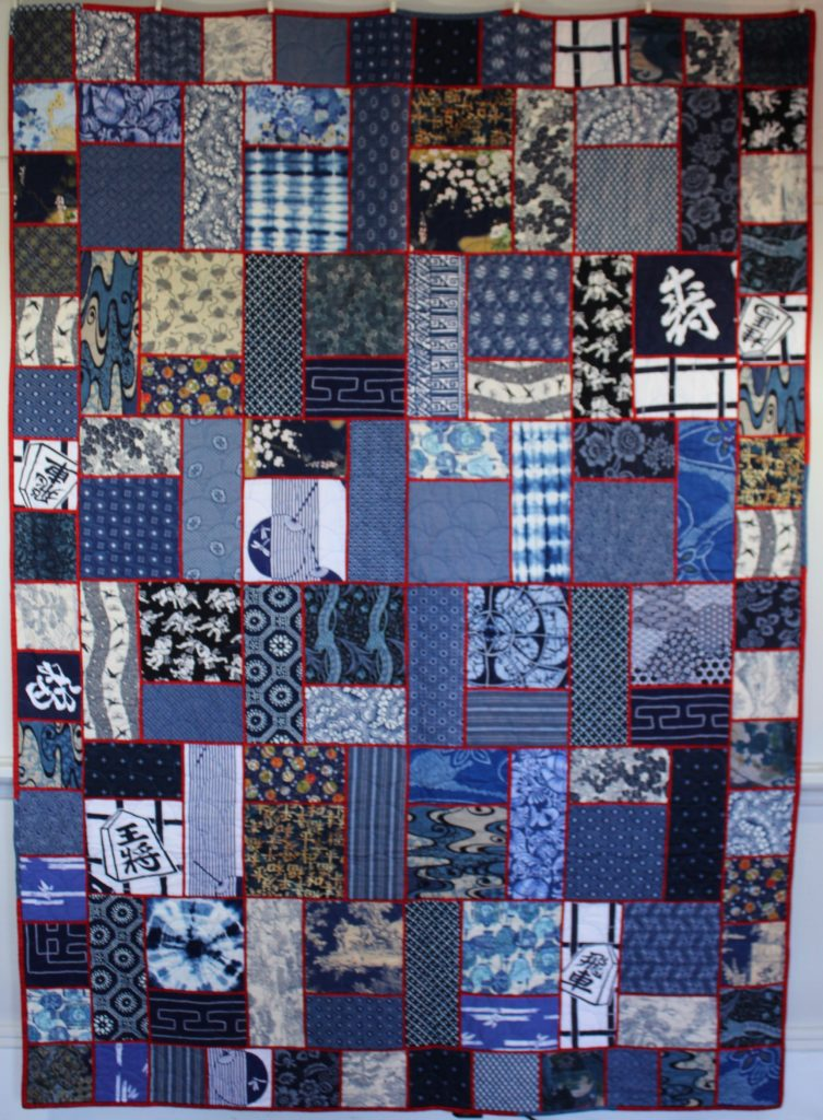 Indigo Sampler with fabrics from Japan, France, Holland, South Africa, China, Tibet, United States and hand dyed shibori. Pattern is Basement Floor by Sharon Mayers of Piecing with Poppers.